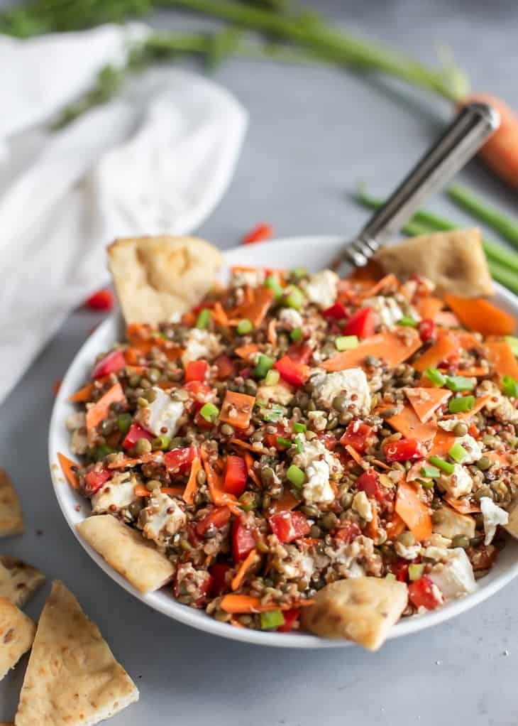 large serving bowl with quinoa lentil salad tossed in a maple balsamic dressing, served with pita chips