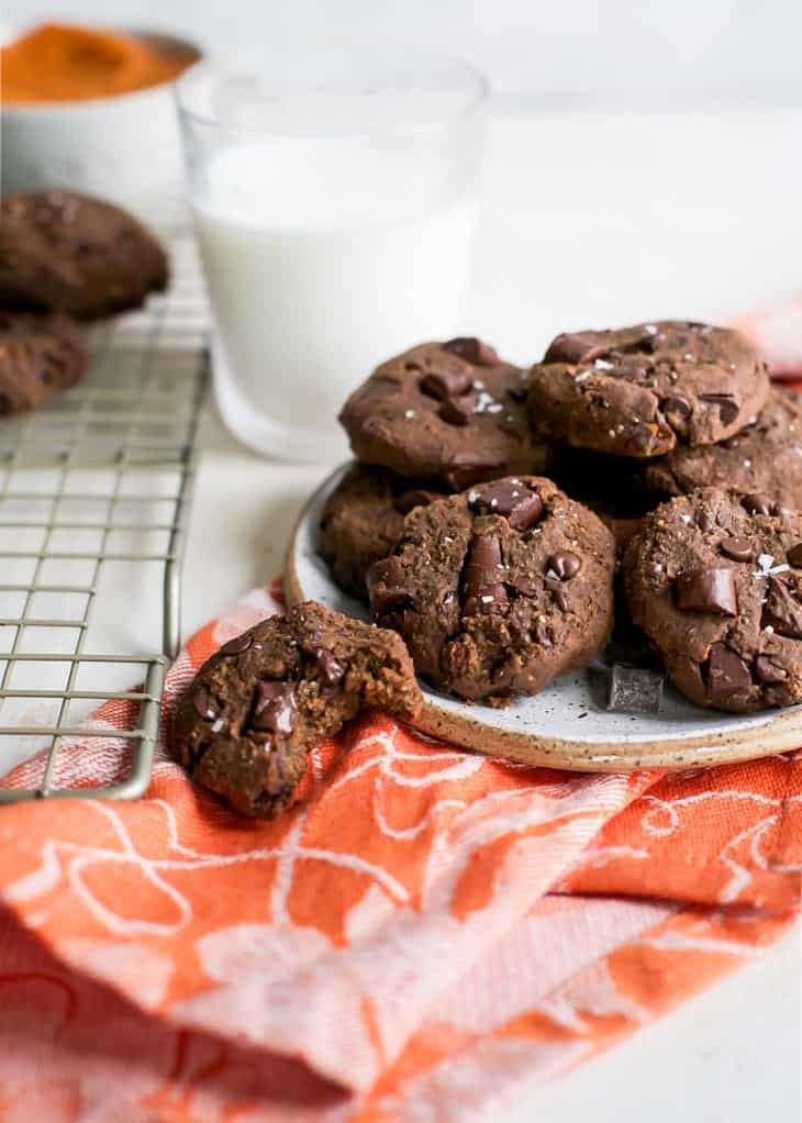 plate of chocolate chickpea cookies on orange towel and pottery plate