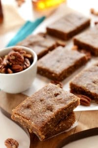 paleo pecan pie bars with pecans in small white bowl