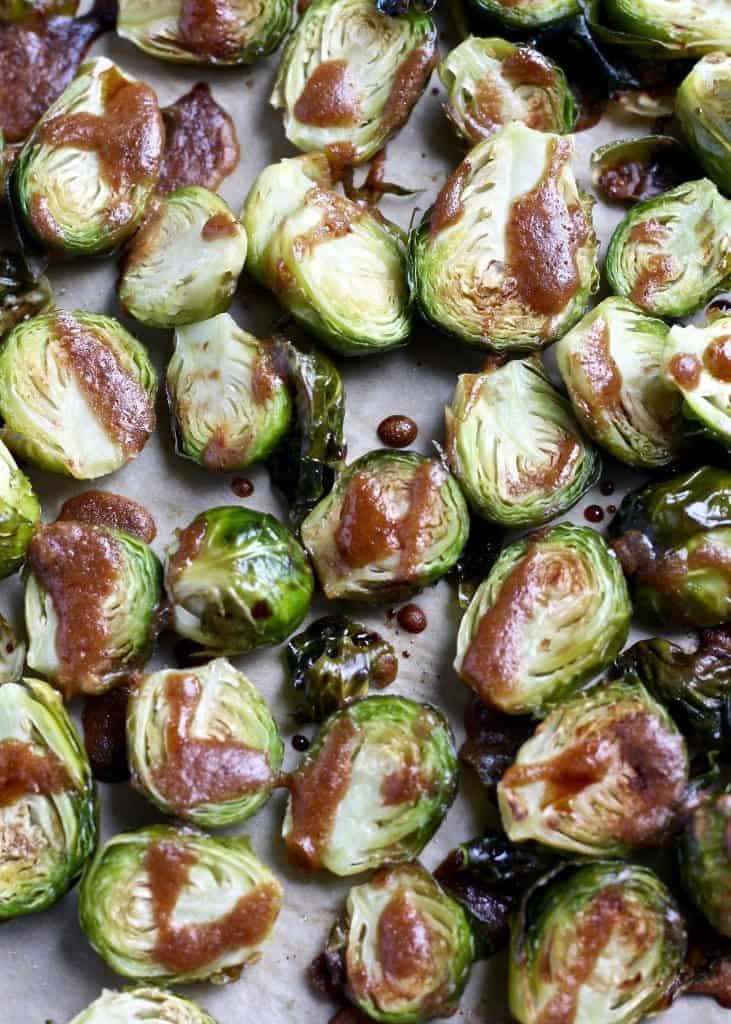 Close up of Roasted Brussels Sprouts with Balsamic Almond Dressing on baking sheet
