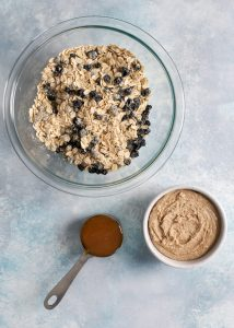 bowl of oats and dried blueberries with honey and cashew butter in bowl