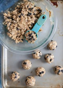 blueberry coconut oat energy ball mixture in glass bowl with tablespoon on baking sheet