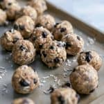 coconut oat energy balls with dried blueberries on baking sheet