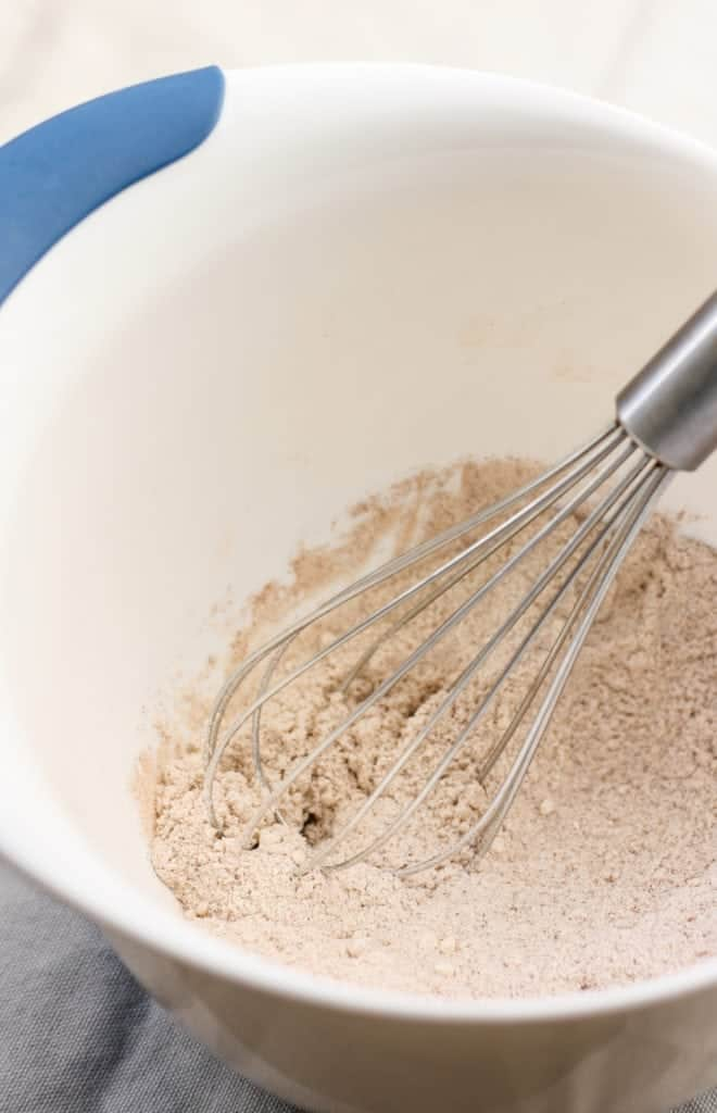 coconut flour dry ingredients in white bowl with whisk