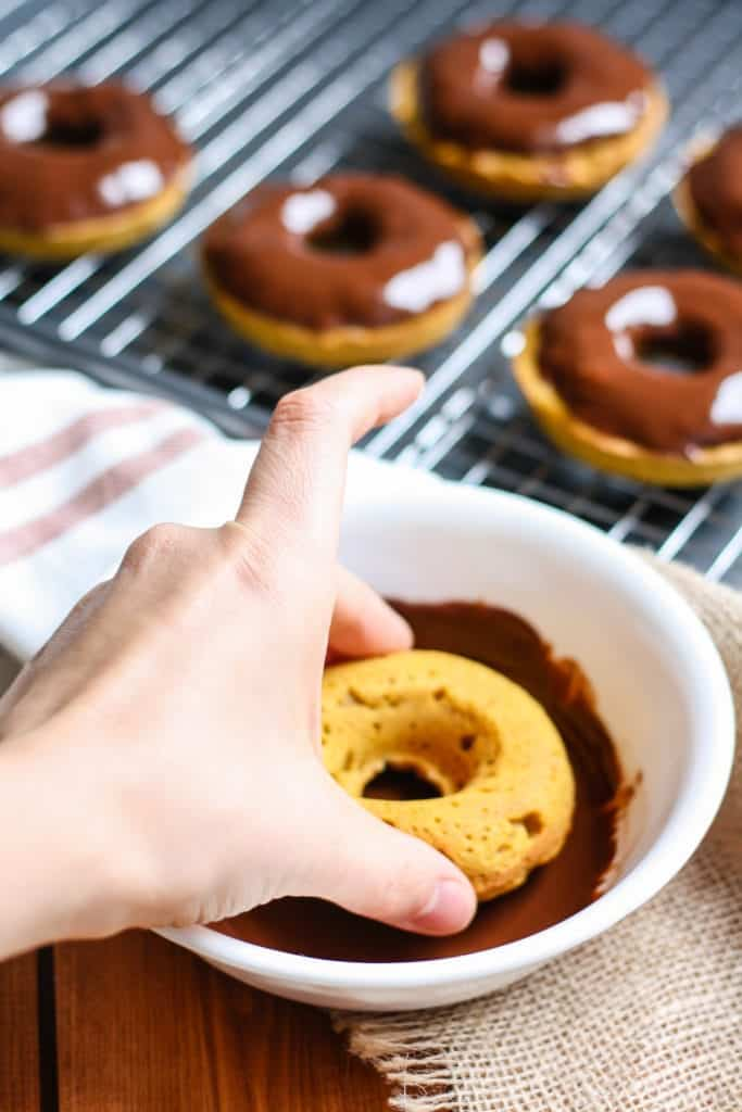Whole Wheat Pumpkin Donuts dipping in chocolate glaze