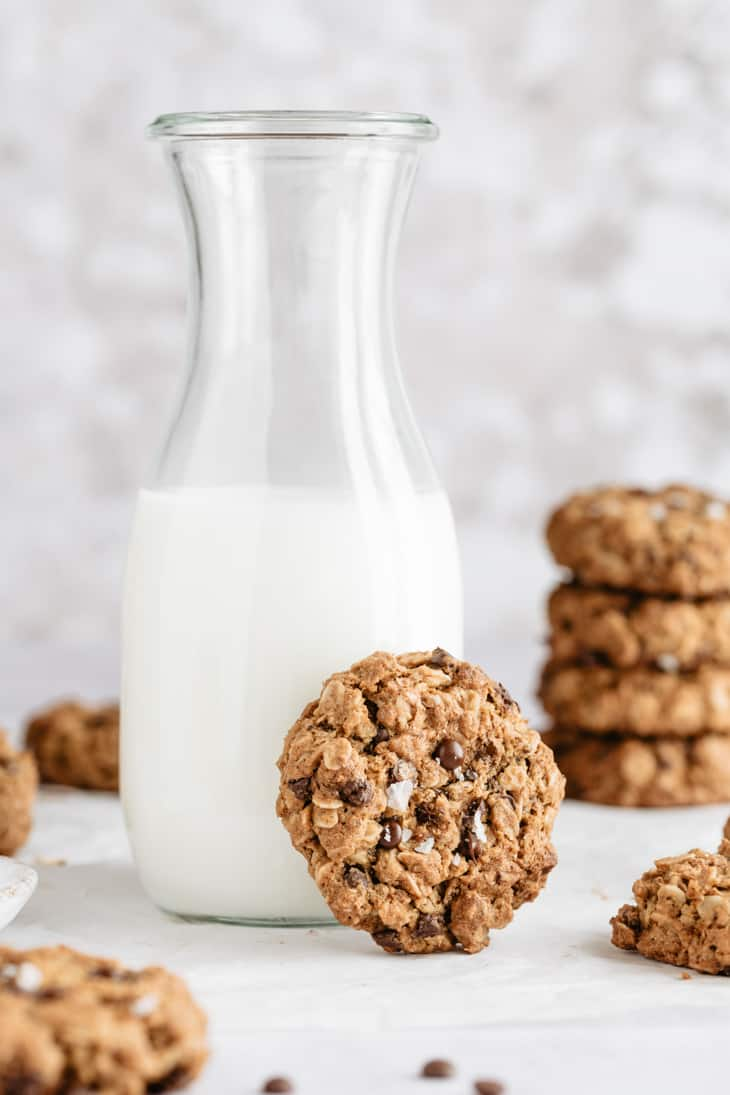 oatmeal chocolate chip cookie next to milk glass