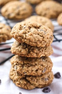stack of healthier whole wheat oatmeal chocolate chip cookies with cooling rack in background