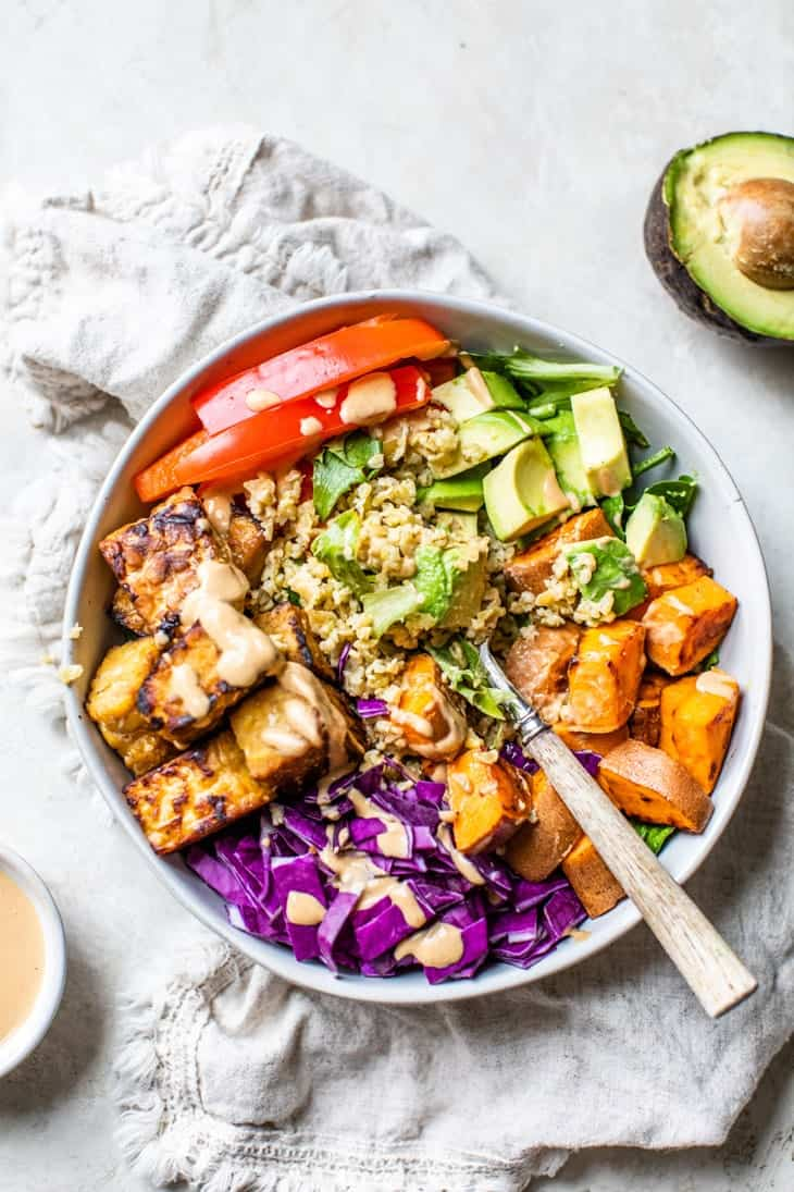 thai tempeh buddha bowl with dressing and avocado