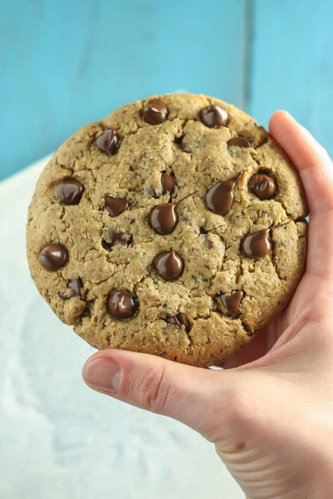 Giant Vegan Chocolate Chip Cookie closeup in hand with blue background