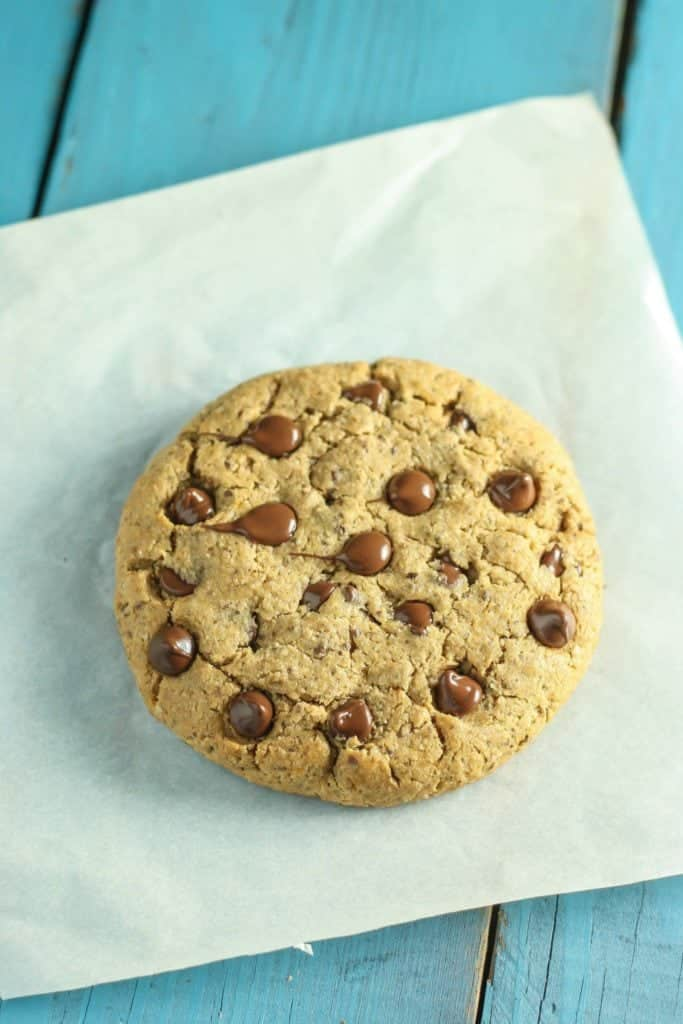 Giant Vegan Chocolate Chip Cookie on parchment paper with blue background