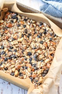 homemade snack bars in baking sheet with parchment paper lining
