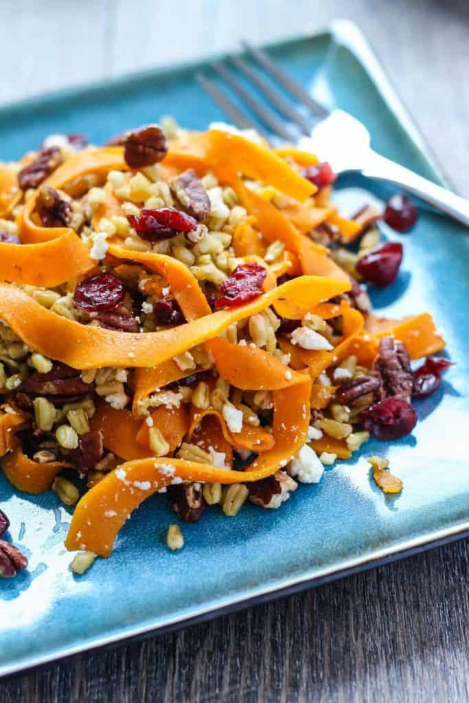 Butternut Squash Freekeh Salad with cranberries, feta, and pecans on blue plate with fork