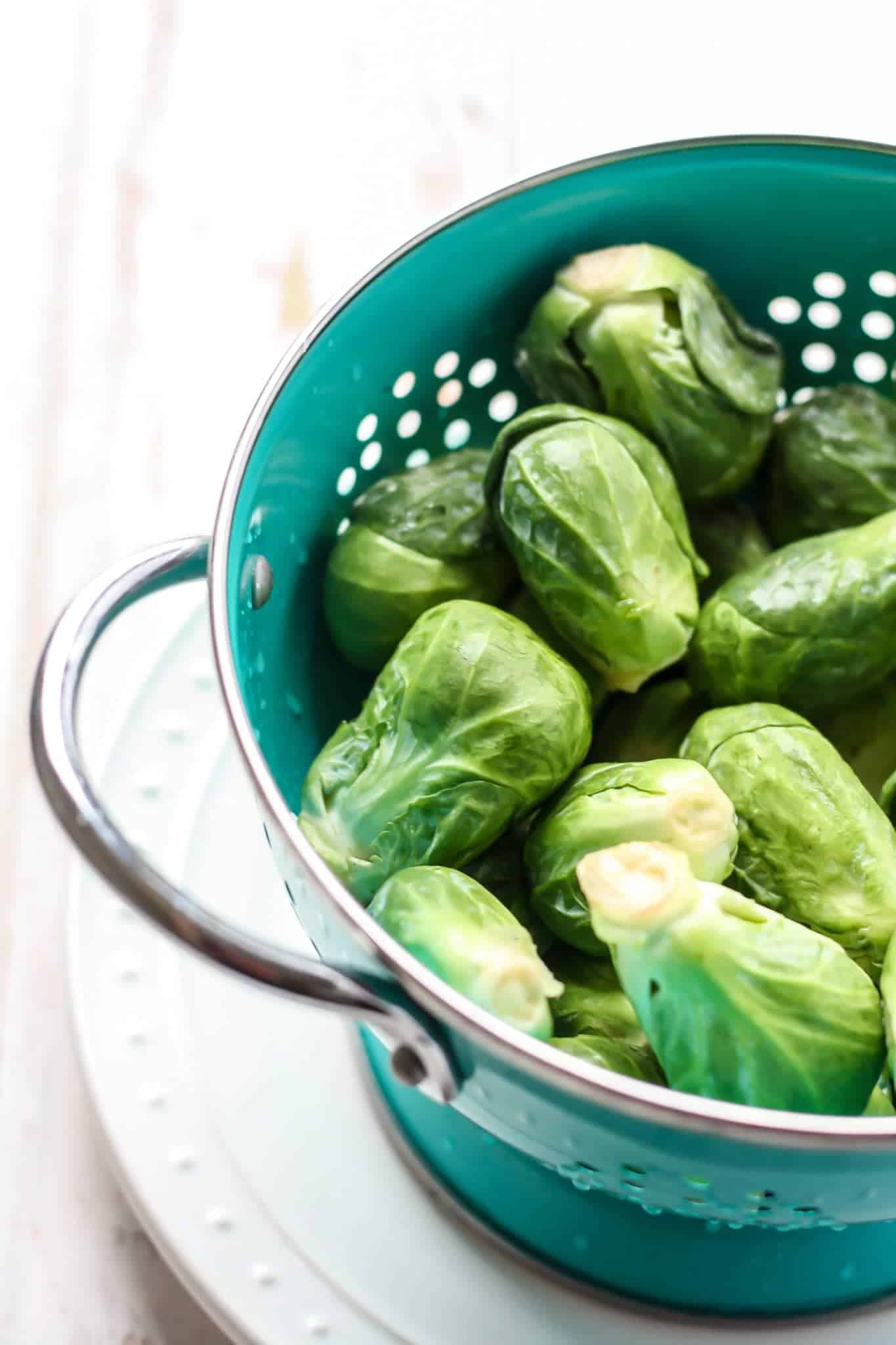 brussel sprouts in teal strainer