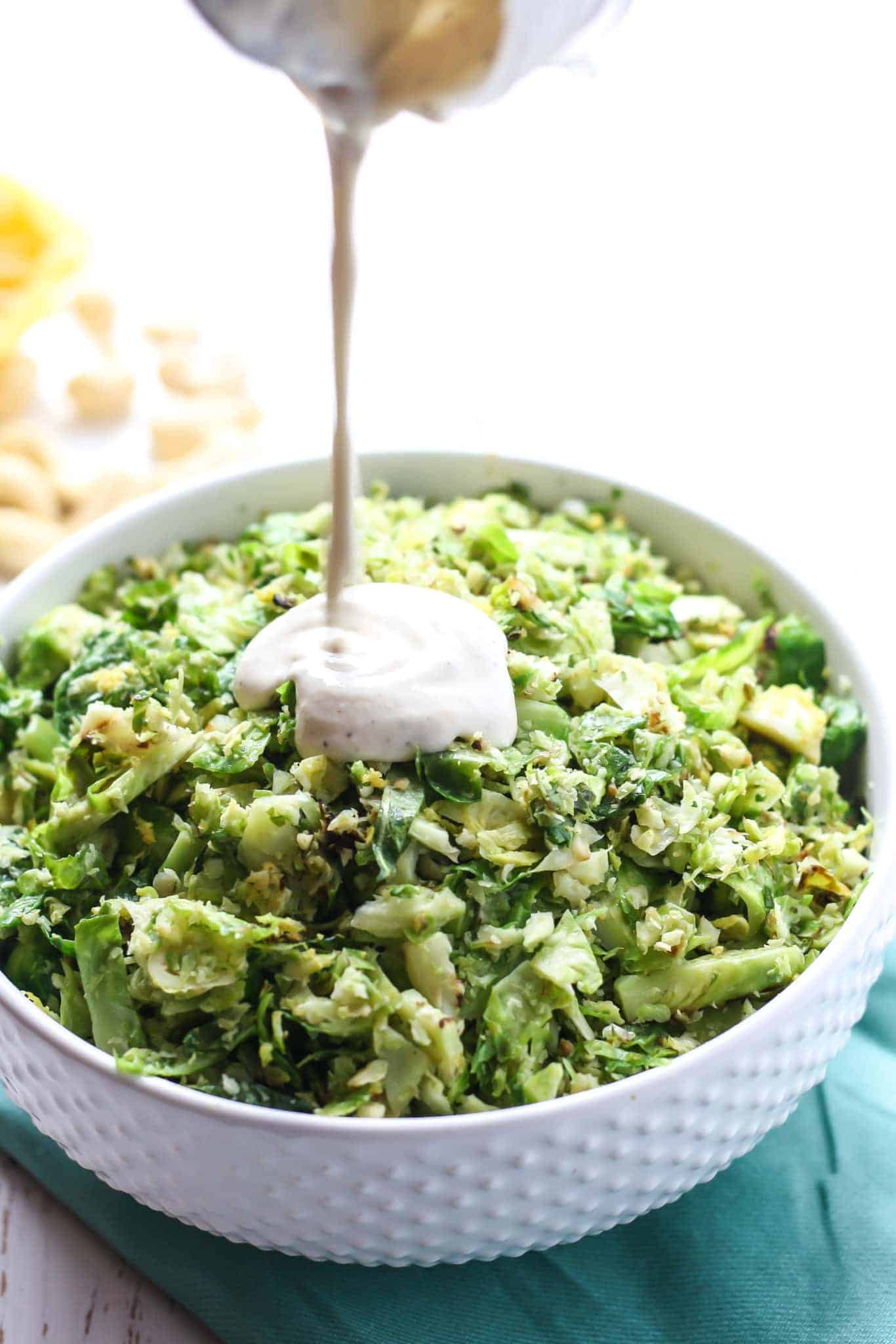 shredded brussels sprouts salad with lemon pepper cashew dressing being poured in white bowl