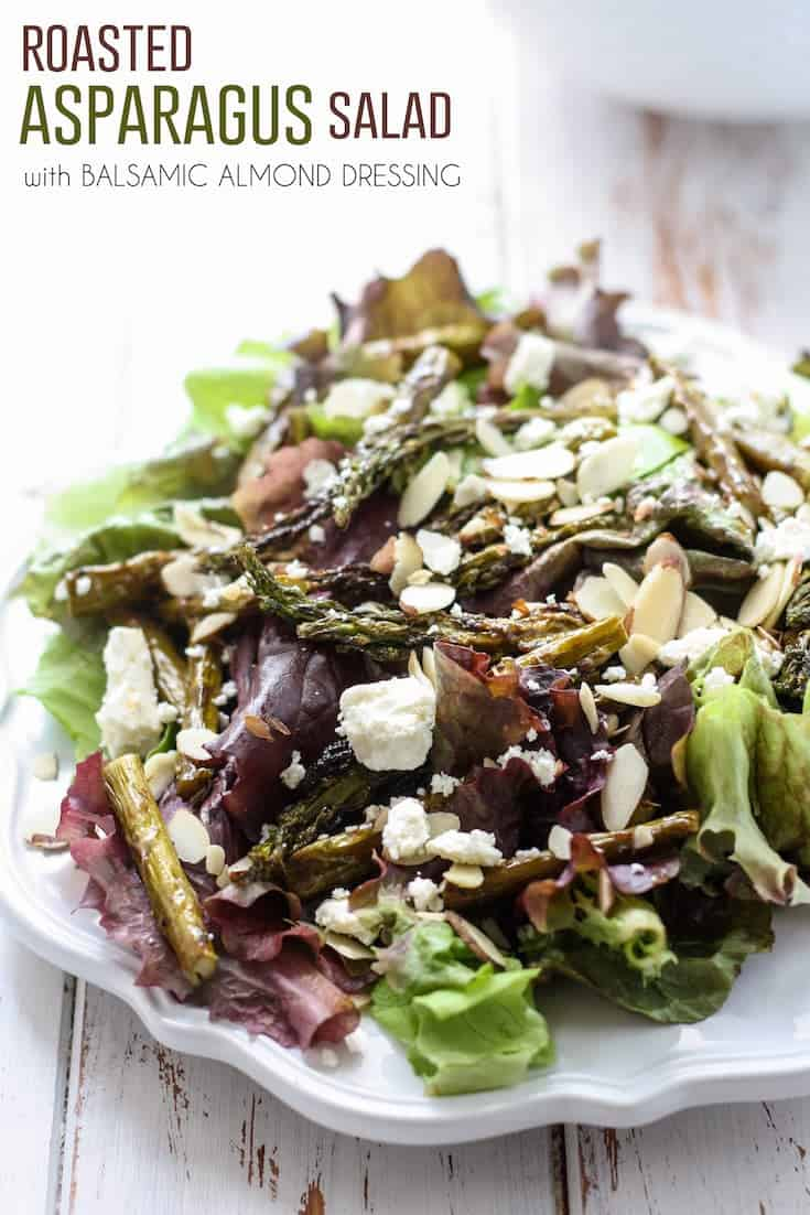 roasted asparagus salad with feta cheese and sliced almonds on white plate