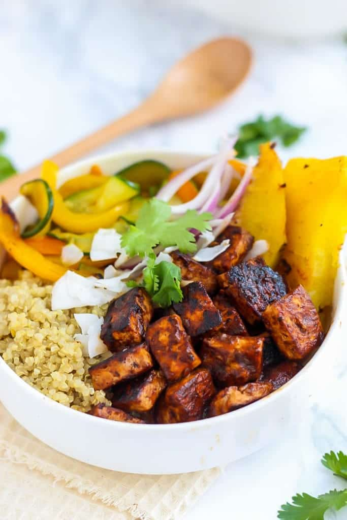 Close up of Vegan Hawaiian BBQ Tofu Bowls in white bowl and wooden spoon