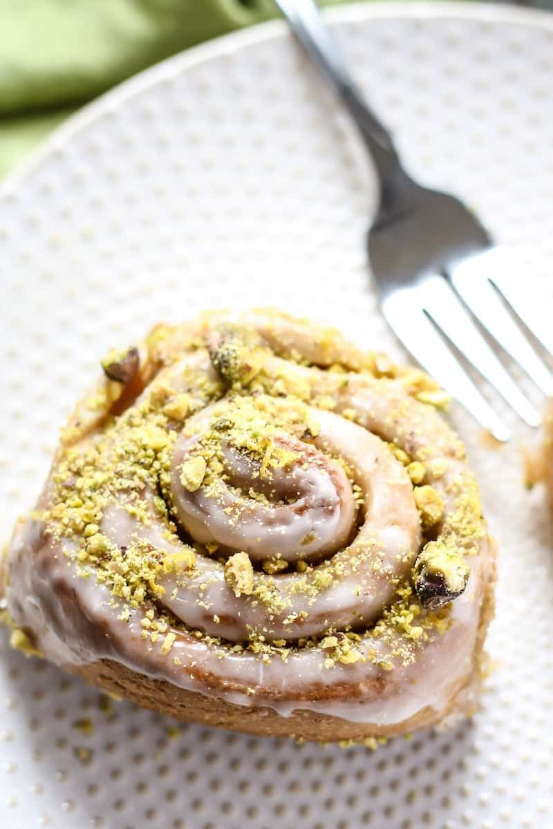 Vegan Whole Wheat Lemon Pistachio Sweet Rolls on white plate with fork