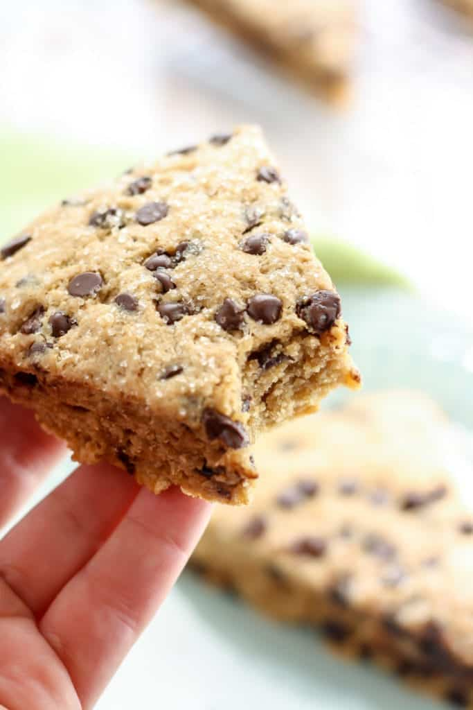 hand holding a bite out of a vegan whole wheat chocolate chip scone