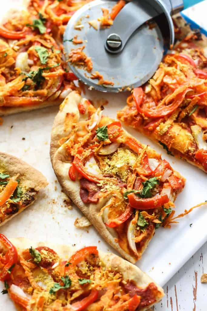 easy vegan thai naan pizza on cutting board with pizza cutter