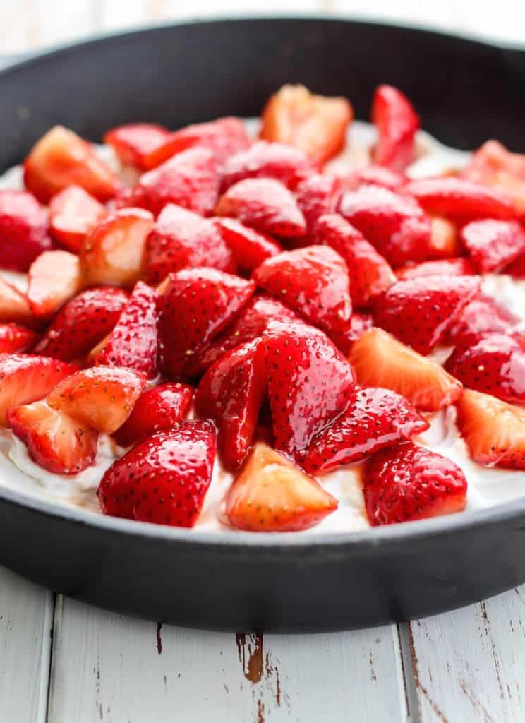 pile of juicy strawberries topped on coconut cream and a paleo shortcake in a cast iron skillet