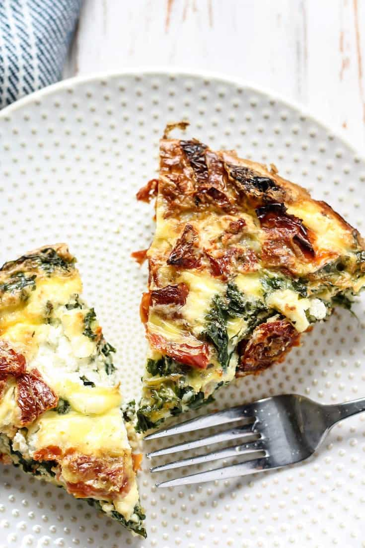 Kale & Goat Cheese Egg Bake with Sun-Dried Tomatoes on white plate with fork