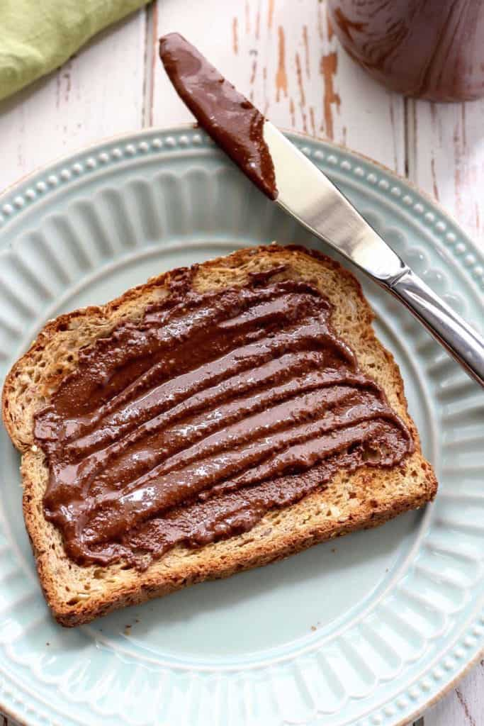 Chocolate Pecan Almond Butter on toast on plate with knife