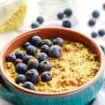 Golden Milk Overnight Oats with blueberries in teal and orange bowl