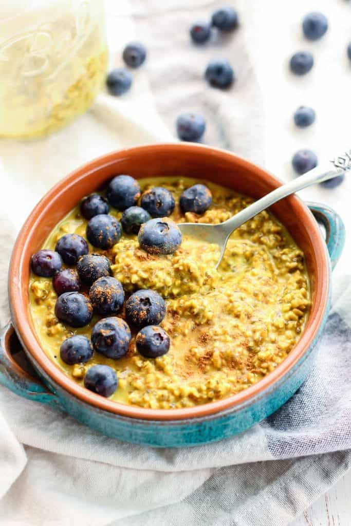 Golden Milk Overnight Oats with blueberries in teal and orange bowl with spoon