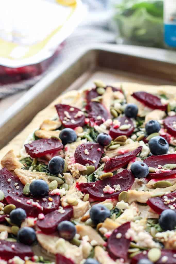 A crazy good combo of flavors here in this pomegranate balsamic marinated chicken & beet goat cheese flatbread. Then we're topping it off with blueberries, pepitas, and hemp hearts!