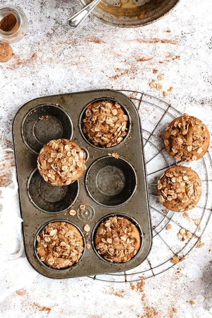 apple cinnamon muffins in pan cooling on rack