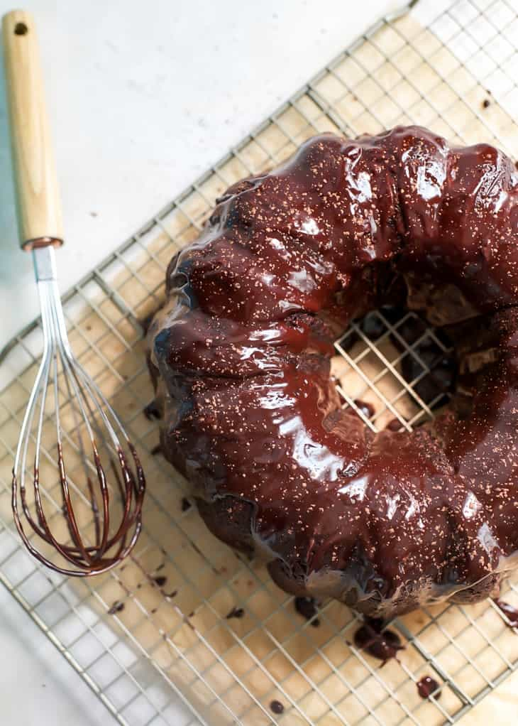 bundt cake chocolate zucchini cake on cooling rack with whisk
