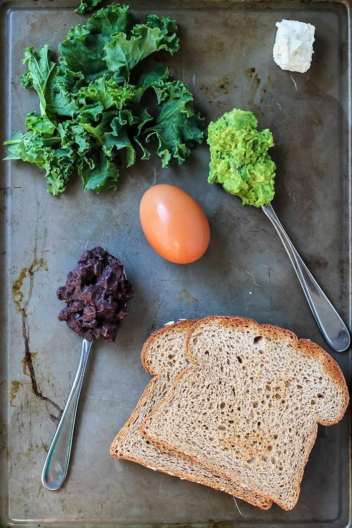 avocado black bean breakfast sandiwch with kale egg avocado mashed black beans on baking sheet