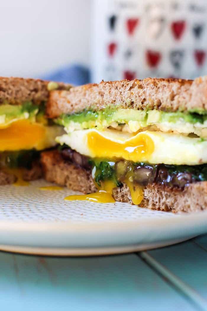 Breakfast sandwich with egg avocado black beans kale feta on white plate