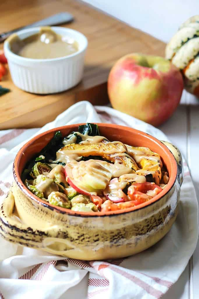 Fall Harvest Power Bowl with brussel sprouts apples tahini dressing in orange bowl