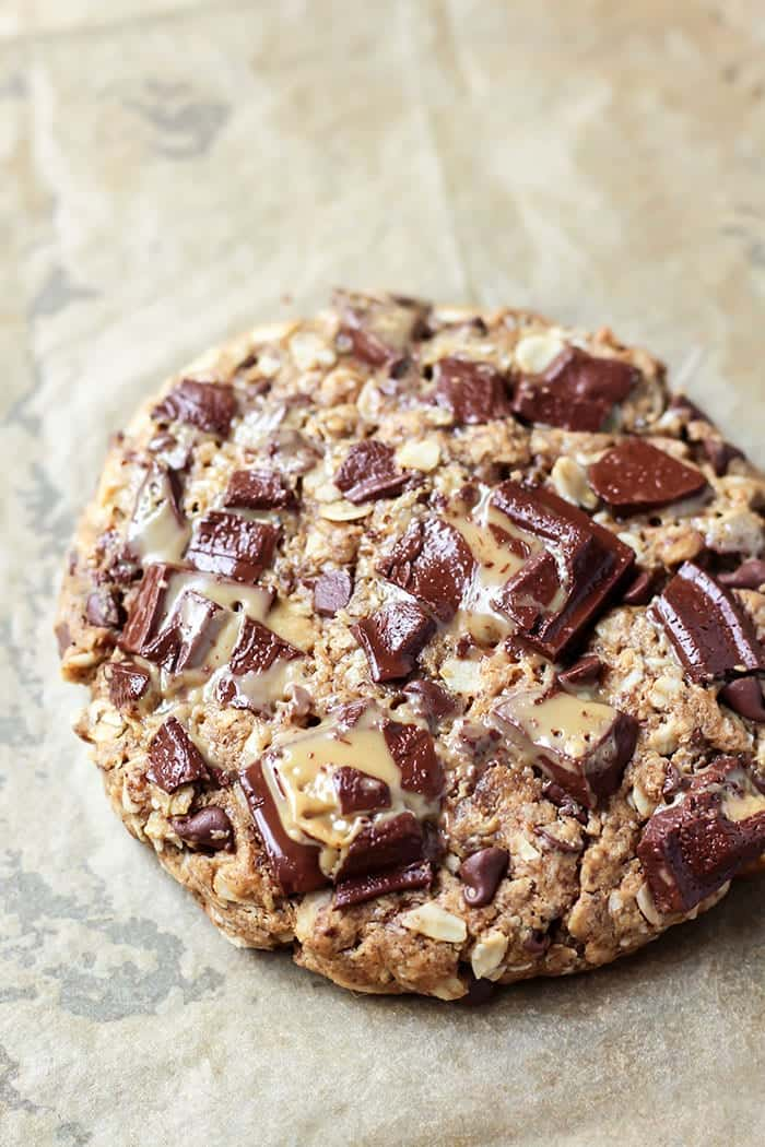 Oatmeal caramel chocolate chip giant cookie on parchment paper