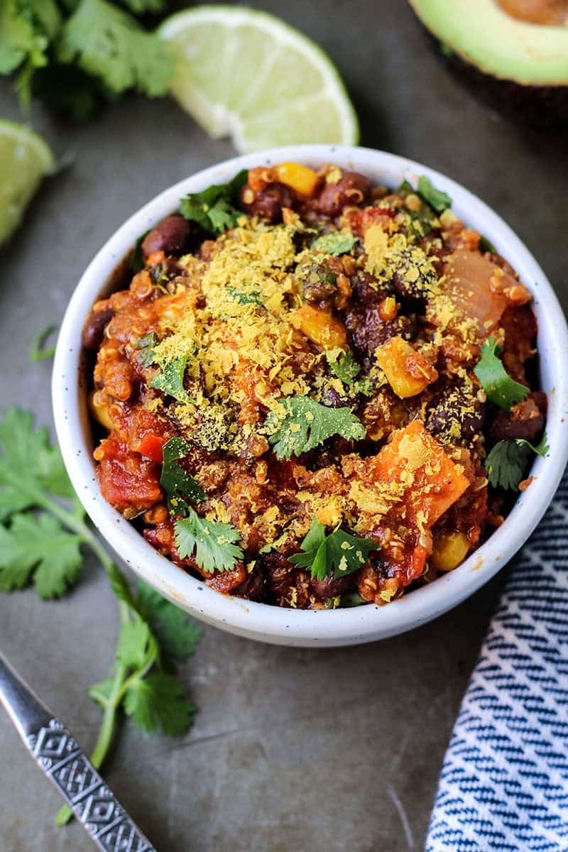 Slow Cooker Vegan Enchilada Quinoa Chili in white bowl with cilantro lime and avocado