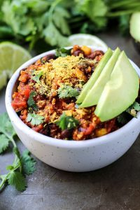 vegan crockpot recipe with quinoa, enchilada sauce and avocado slices in white bowl with lime wedges and cilantro