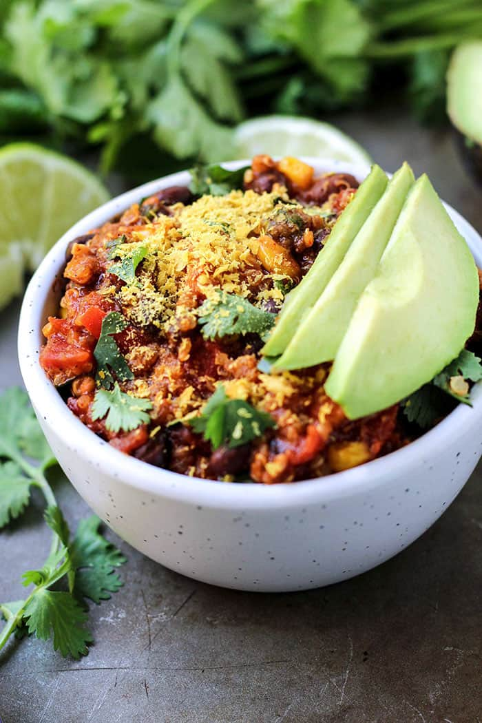 Vegan Enchilada Quinoa Chili in white bowl with avocado slices cilantro lime