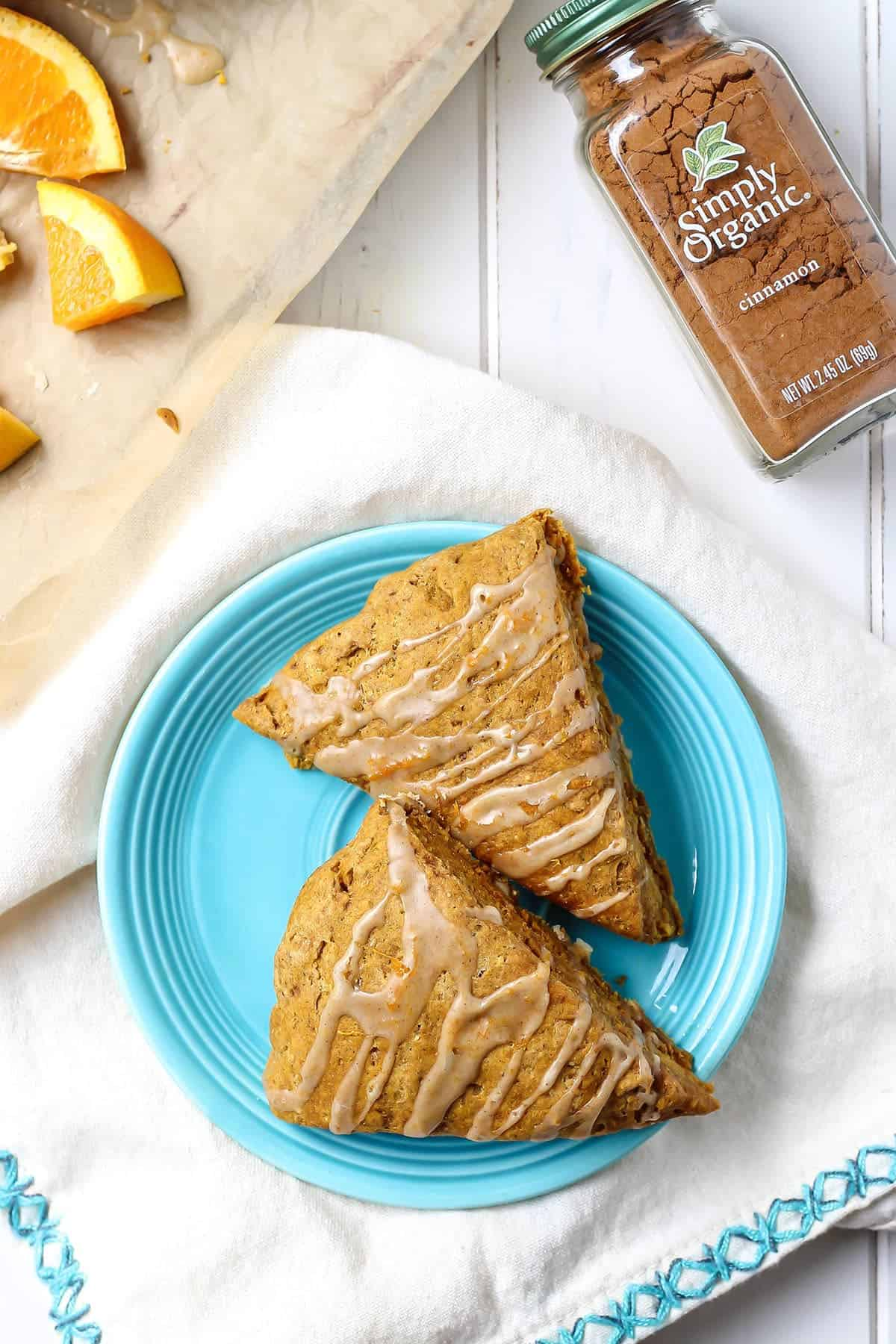 Vegan Pumpkin Scones on blue plate with oranges and cinnamon