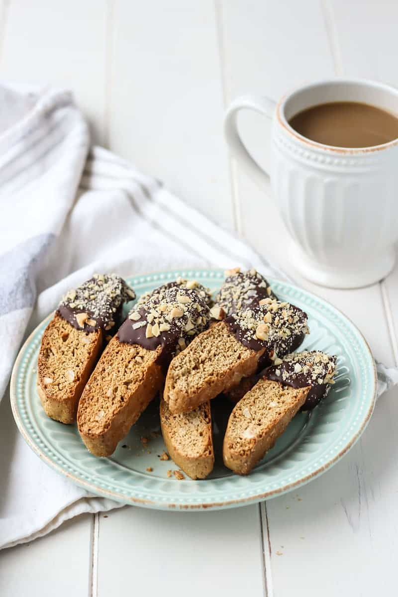 Whole Wheat Hazelnut Chocolate Dipped Biscotti on blue plate with cup of coffee in white mug