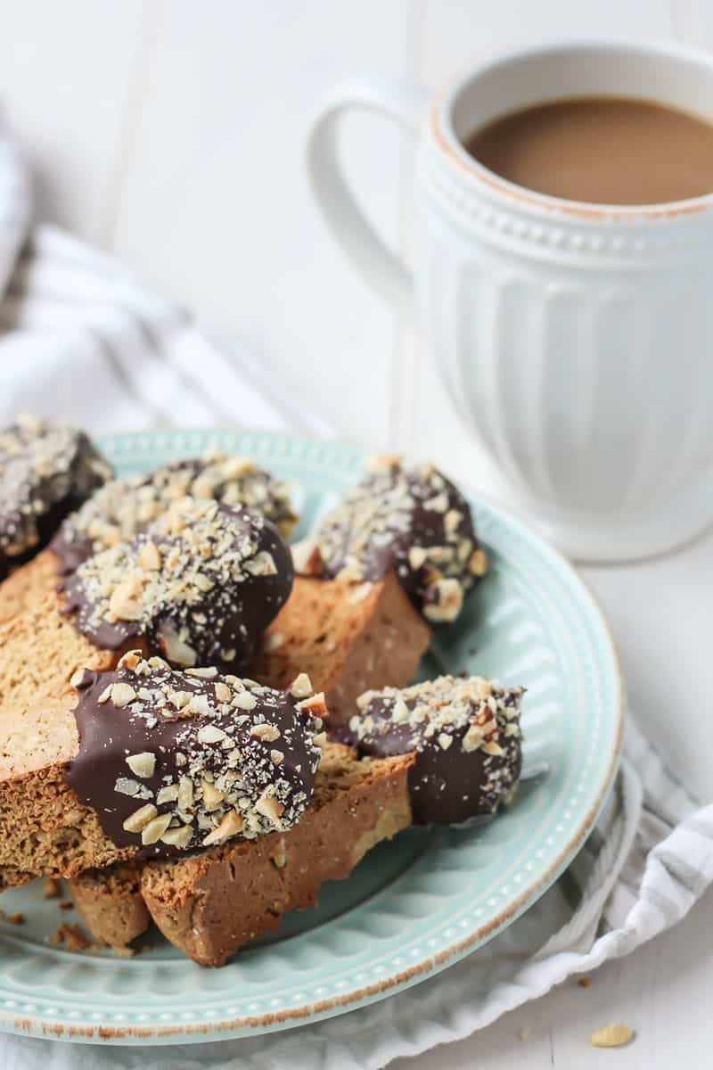 Chocolate dipped hazelnut biscotti on blue plate with cup of coffee in white mug
