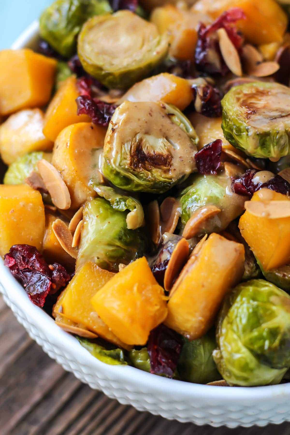 Maple Roasted Brussels Sprouts & Squash with an almond butter balsamic dressing in white bowl