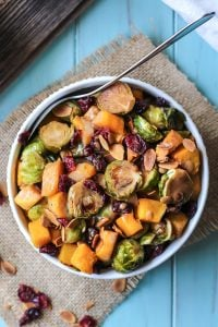 healthy maple roasted brussels sprouts with butternut squash, cranberries and almonds in white bowl with spoon