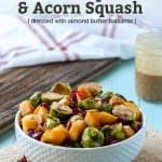 healthy maple roasted brussels sprouts and squash in a white dish with dried cranberries