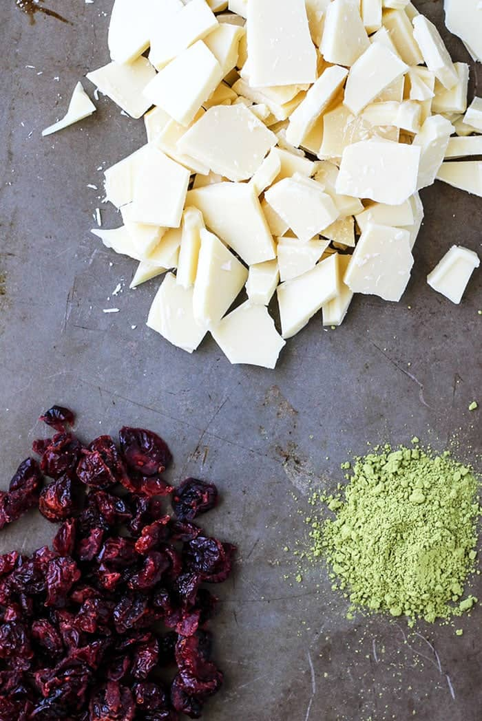 Matcha and dried cranberries and white chocolate on baking sheet