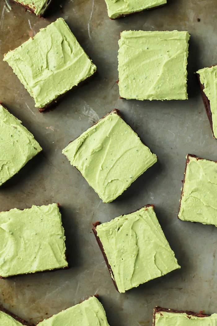 brownies with matcha frosting cut into squares on baking sheet