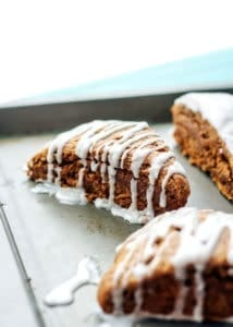 gingerbread scone with vanilla bean icing on baking sheet
