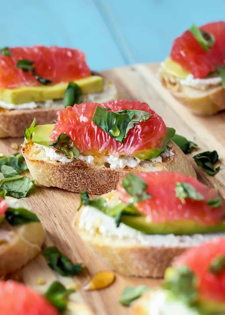 Goat cheese avocado grapefruit crostinis with basil on cutting board