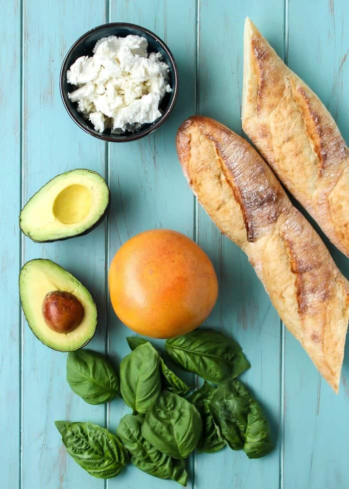 Crostini ingredients goat cheese avocado grapefruit basil and french bread on blue board
