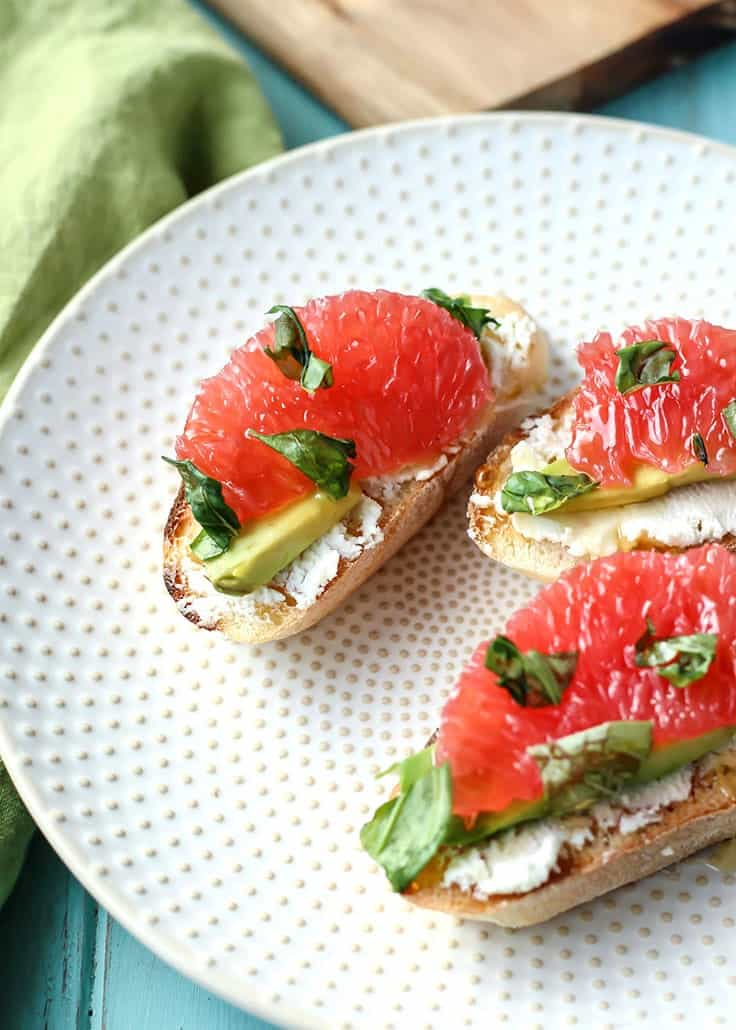 Crostinis with goat cheese avocado grapefruit and basil on white polka dot plate